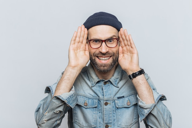 Portrait of happy hipster guy with thick beard and mustache wears stylish hat and glasses