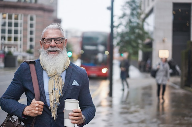 Portrait of happy hipster senior businessman holding a cup of coffee