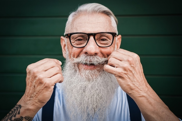 Portrait of happy hipster senior man with green wall - focus on mustache