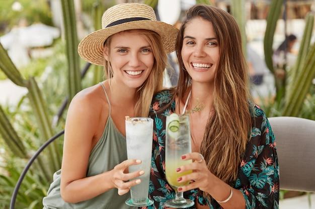 Ritratto di felice coppia omosessuale femminile godersi il riposo estivo, celebrare qualcosa in un accogliente ristorante, tintinnare bicchieri di cocktail, avere ampi sorrisi. bella giovane donna in cappello con un caro amico al bar
