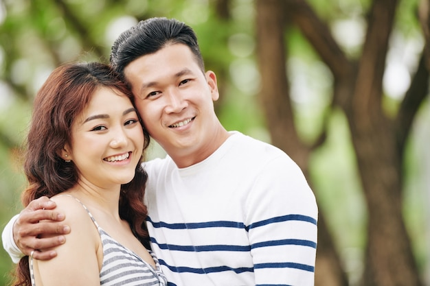 Portrait of happy hugging young asian boyfriend and girlfriend smiling and looking at camera
