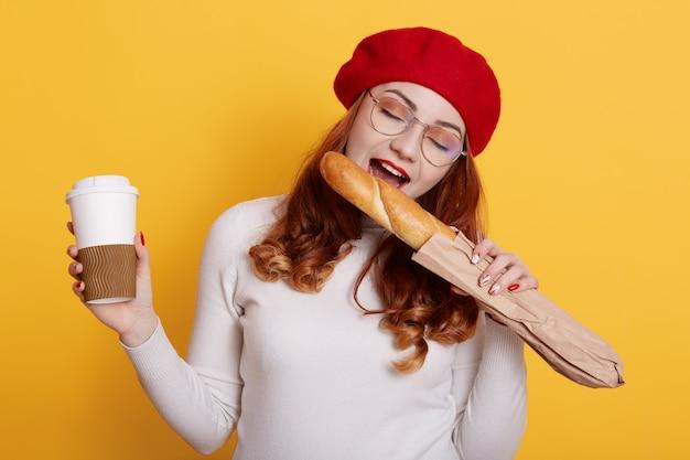 Портрет счастливой голодной женщины, держащей бумажный пакет с длинным багетом из белого хлеба и кусающей его на желтом
