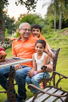 Portrait of happy indian asian kids and grandfather sitting on lawn chair