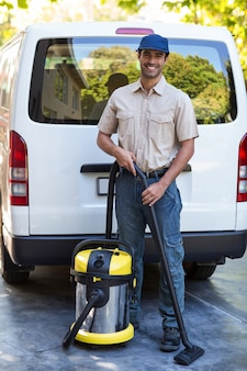 Portrait of happy janitor with vacuum cleaner