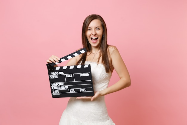 Portrait of happy joyful woman in white dress hold classic black film making clapperboard