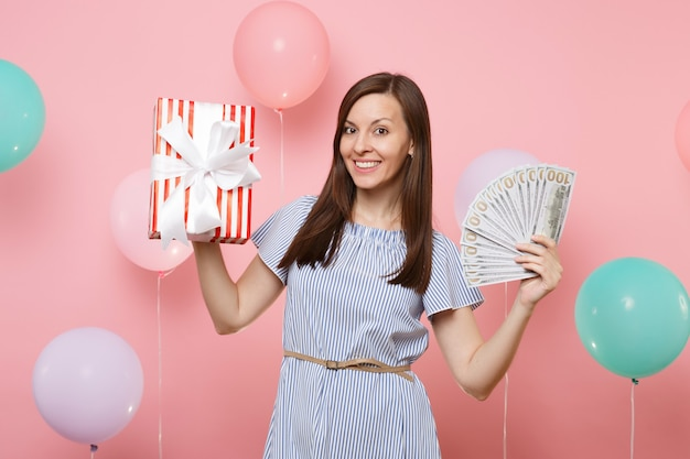 Portrait of happy joyful young woman in blue dress holding bundle lots of dollars cash money and red box with gift present on pink background with colorful air balloon. birthday holiday party concept.