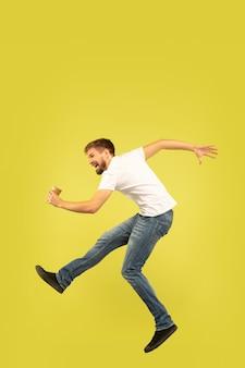 Ritratto di uomo felice che salta sulla parete gialla