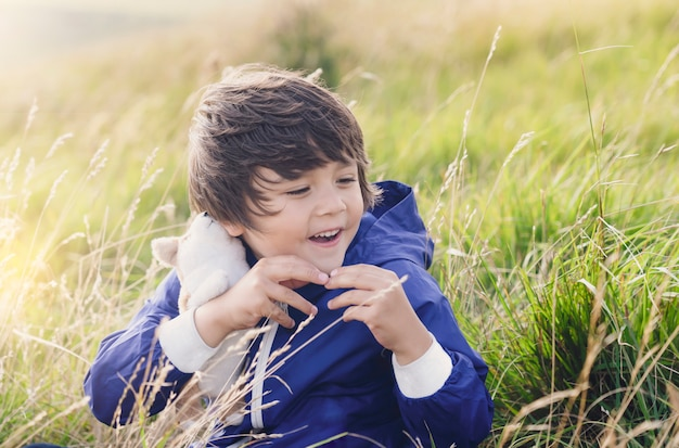 Portrait of happy kid boy showing fluffy dog toy on his hand sitting on grass