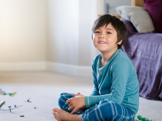Portrait of happy kid looking at camera with smiling face, little boy sitting on carpet relaxing at home