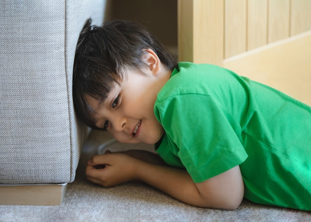 Portrait happy kid lying on carpet hiding behide sofa
