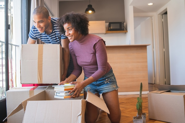Portrait of happy latin couple unpacking at their new house at moving day. real estate concept.
