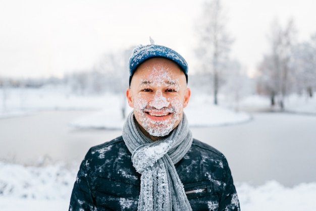 Portrait of a happy laughing man with snow on his face standing outdoor in winter snowy day at nature.