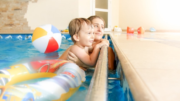 Portrait of happy laughing toddler boy with young mother playing with colorful inflatable beach ball in swimming pool at summer hotel resort