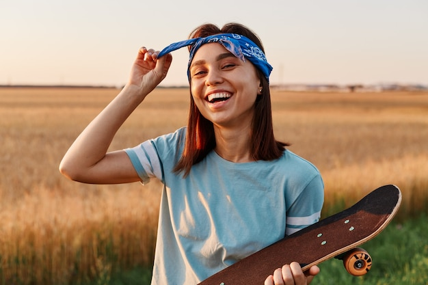 Ritratto di donna che ride felice in posa all'aperto in estate, tenendo lo skateboard in mano, toccando la sua fascia per capelli, guardando la telecamera con emozioni positive.