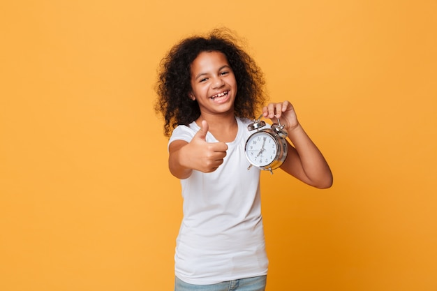 Portrait of a happy little african girl holding alarm clock