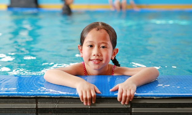 Portrait of happy little asian child girl learning to swim in pool. close-up short.