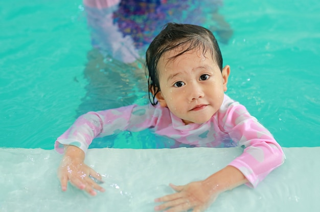 Portrait of happy little asian child girl learning to swim in pool.
