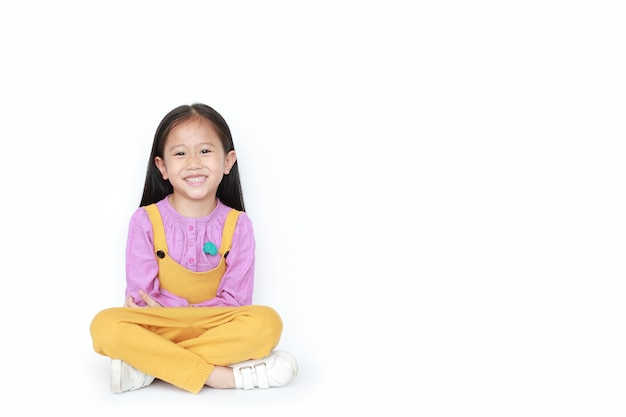 Portrait of happy little asian child girl in pink-yellow pink-yellow dungarees sitting isolated with copyspace.