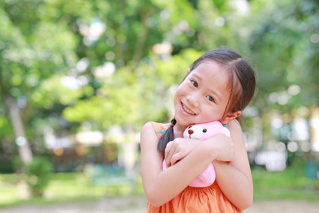 Portrait of happy little asian child in green garden with hugging teddy bear and looking at camera.