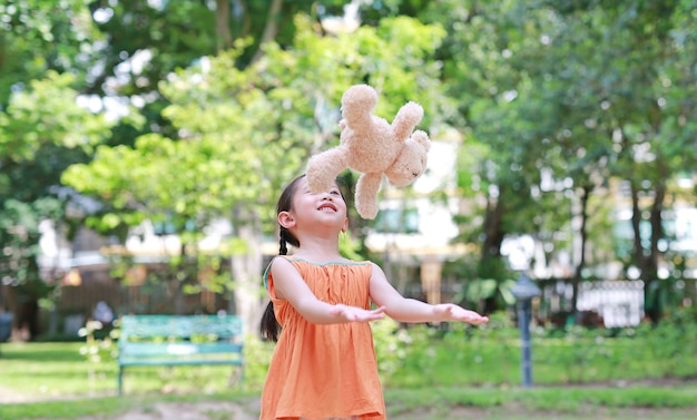 Portrait of happy little asian child in green garden with throwing up teddy bear doll floating on air. smiling kid girl playing in summer park.