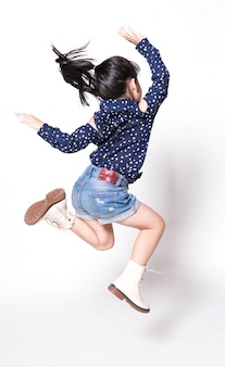 Portrait of happy little asian child jumping isolated on white background