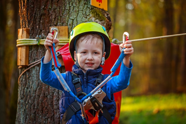 Portrait of happy little boy having fun in adventure park smiling to camera wearing helmet and safety equipment.