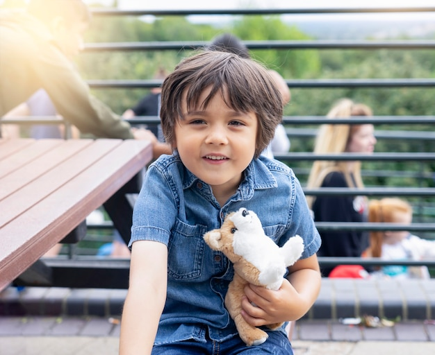 Portrait of happy little boy hugging dog toy siting on wooden bench and making funny face