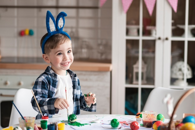 Portrait of happy little boy painting easter eggs