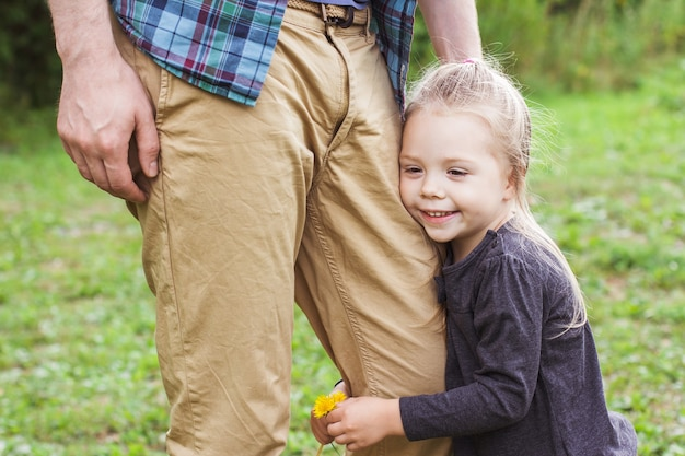 Portrait of a happy little girl (2-3 years old) holding on to her dad's leg. father's day, the relationship of father and daughter.