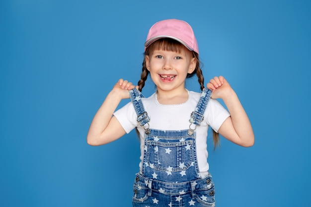 Portrait of a happy little girl 5-6 years old in a cap, on a blue wall isolate, place for text. toothless baby. sun protection.