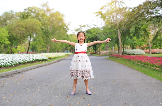 Portrait of happy little girl closed eyes and open wide her arms standing on road in the garden.