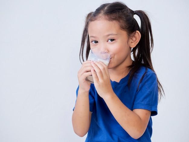 Portrait of happy little girl drinking milk from glass on light