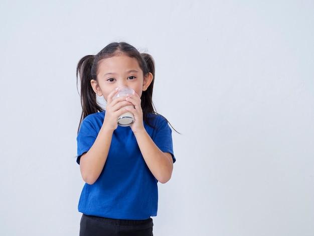 Portrait of happy little girl drinking milk on light