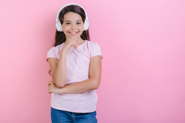 Portrait of happy little girl in earphones listening to music and looking at the camera