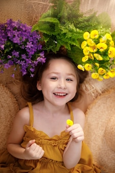 Portrait of a happy little girl lying with flowers and straw hat, summer and travel feeling concept
