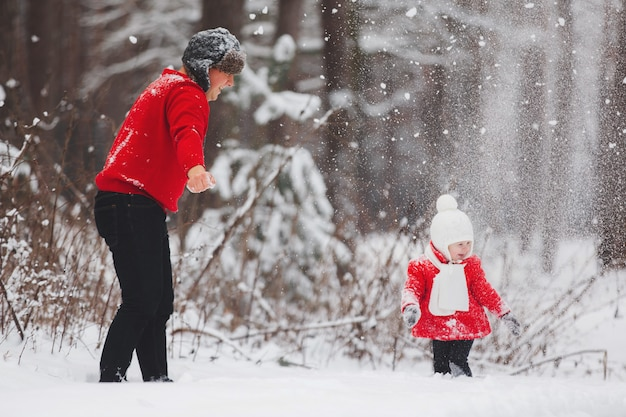 Portrait of happy little girl in red coat with dad having fun with snow in winter forest. girl playing with dad.