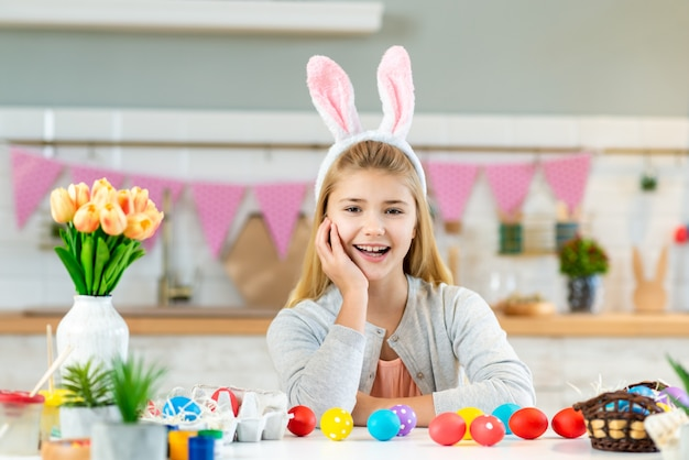 Portrait of happy little girl sitting at the table and happily smiling wearing bunny ears.