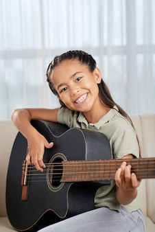 Portrait of happy little girl smiling at camera while sitting on sofa and learning to play guitar
