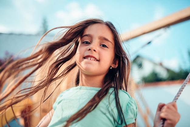 Portrait of a happy little girl on a swing