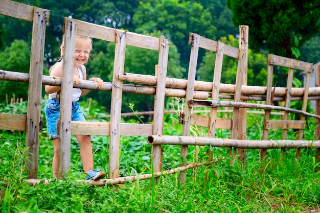 Portrait of happy little girl with blonde hair on a wooden fence