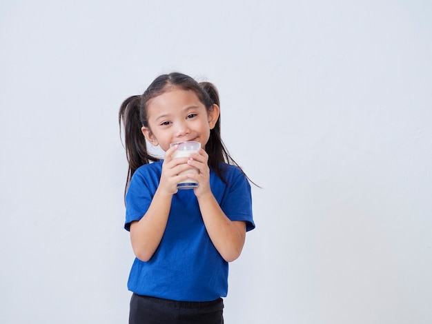 Portrait of happy little girl with glass of milk on light