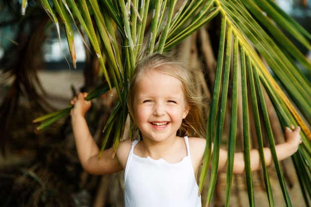 Portrait of happy little girl with palm leaf.