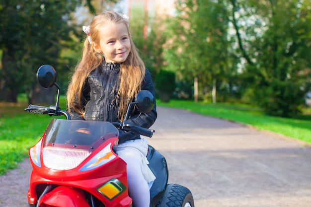 Portrait of happy little rock girl in leather jacket sitting on her toy motorcycle