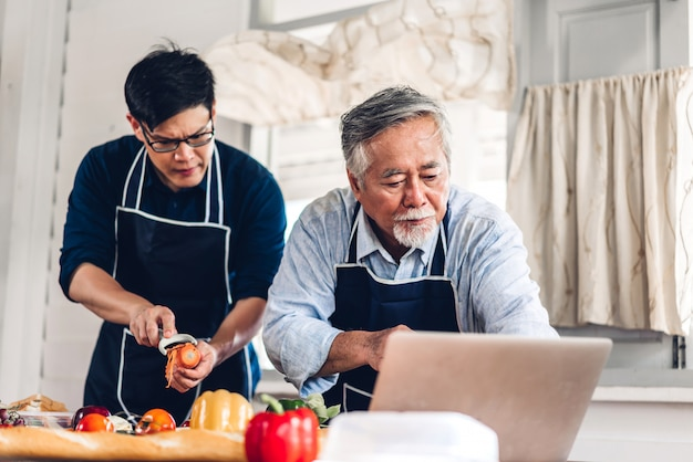 Portrait of happy love asian family senior mature father and young adult son having fun cooking together and looking for recipe on internet with laptop computer