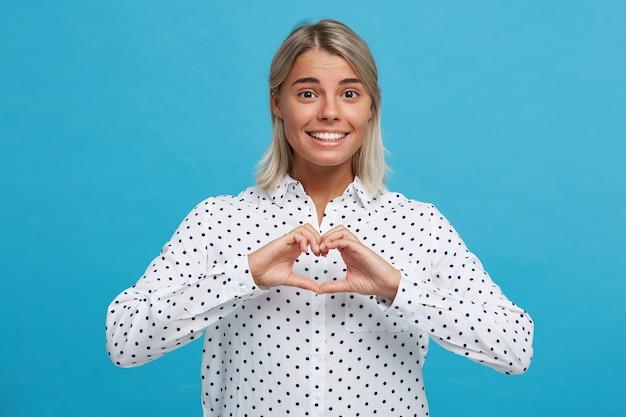 Il ritratto della giovane donna bionda adorabile felice indossa la camicia del puntino di polka che sorride e che mostra la forma del cuore dalle mani isolate sopra la parete blu