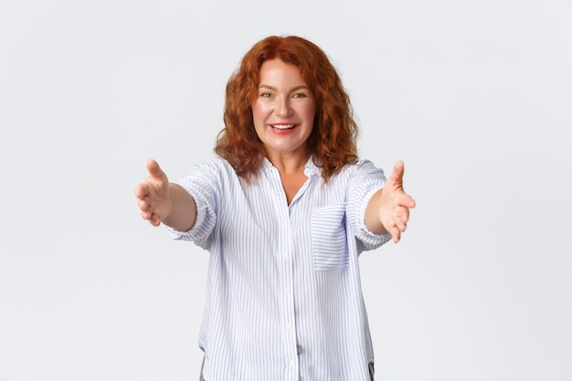 Portrait of happy and lovely redhead middle-aged woman extend hands, reaching arms for hug, mother wanting to cuddle or embrace someone. female receive gift and taking it, white background.