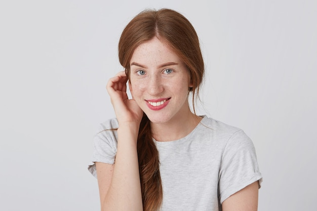 Portrait of happy lovely redhead young woman with freckles wears gray t shirt touching her ear