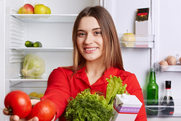 Portrait of happy lovely woman with cheerful expression dressed in red blouse, holds fresh vegetables, demonstrates red tomatoes, being glad to start new day, makes vegeterian salad for herself