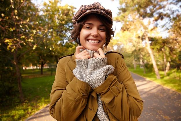 Ritratto di felice bella giovane donna bruna con bob acconciatura sorridente ampiamente mentre guarda e mantenendo le mani alzate sul suo poloneck lavorato a maglia, in posa all'aperto in giornata di sole