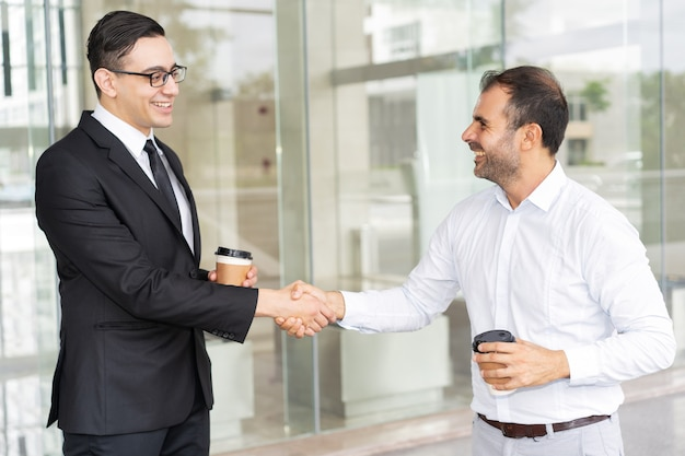Portrait of happy male business partners shaking hands
